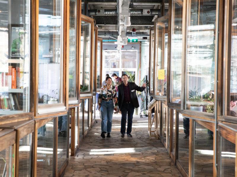 Mensen lopen door BlueCity. Symmetrische foto van glazen gang.