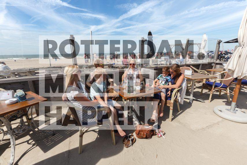Hoek van Holland: Mensen met kinderen op terras aan strand Hoek van Holland.