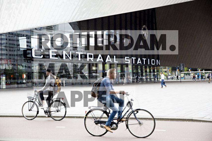 Fietsers rijden voorbij Rotterdam Centraal dat ontworpen is door Benthem Crouwel Architekten.