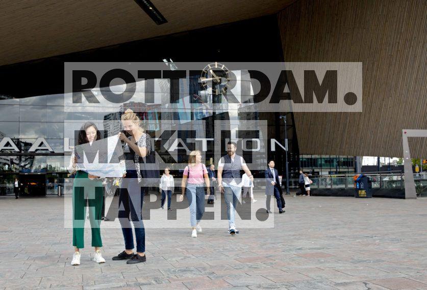 Toeristen bekijken de kaart van Rotterdam op het Stationsplein.