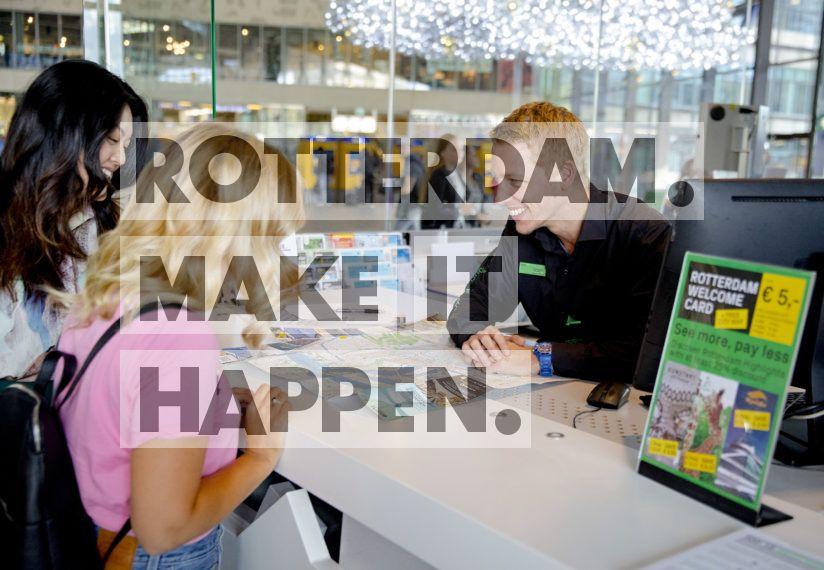 Toeristen worden geholpen aan de balie van de Rotterdam Tourist Information.