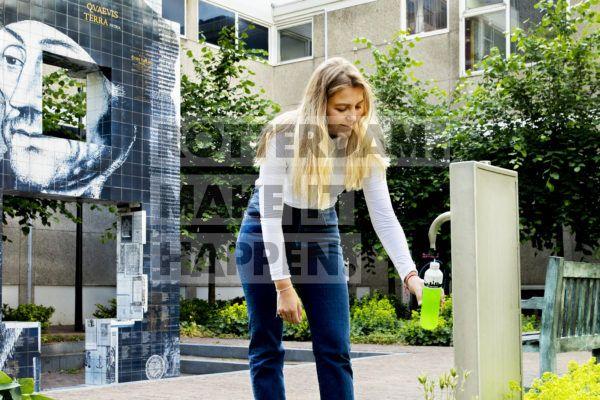 Vrouw bij drinkwaterpunt en Erasmus monument.