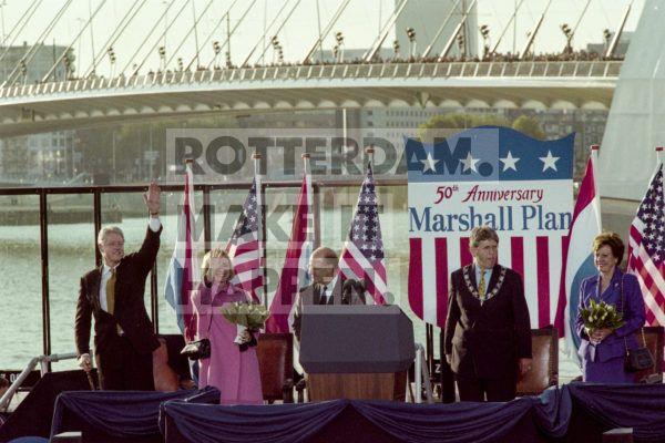 Hoog bezoek! In 1997 stond Nederland stil bij de Marshallhulp. Mede dankzij deze hulp kwam het naoorlogse Nederland vijftig jaar geleden weer op de been. Het Marshall Plan was een omvangrijk materieel hulpplan, dat op initiatief van de toenmalige Amerikaanse minister van Buitenlandse Zaken George C. Marshall drie jaar na de Tweede Wereldoorlog in werking trad. Voor deze gelegenheid brachten president Bill Clinton en zijn vrouw Hillary een bezoek aan Rotterdam. Oud-burgemeester Bram Peper en zijn toenmalige echtgenote Neelie Kroes waren bij de ceremonie aanwezig.