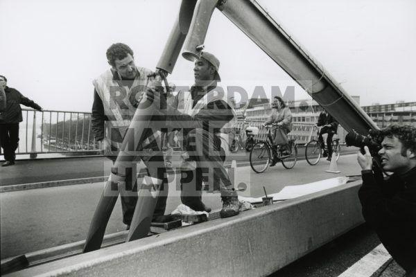 'Zouwe de touwe 't houwe' was in oktober 1996 een gevleugelde uitspraak toen bleek dat de Erasmusbrug bij windkracht zes begon te slingeren. Het brugdek is opgehangen aan tuidraden, vergelijkbaar met pianosnaren die een bepaalde toon kunnen geven. Werknemers van de schokdemperfabrikant Koni uit Oud-Beijerland monteren schokdempers in de tuien van de Erasmusbrug, die in staat zijn ongewenste trillingen op te vangen. Een slim staaltje techniek dat later in veel andere landen zou worden toegepast!